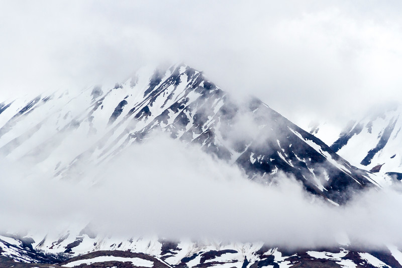 Stormy weather and snow covered mountains in Alaska Mountain Range in Denali National Park.