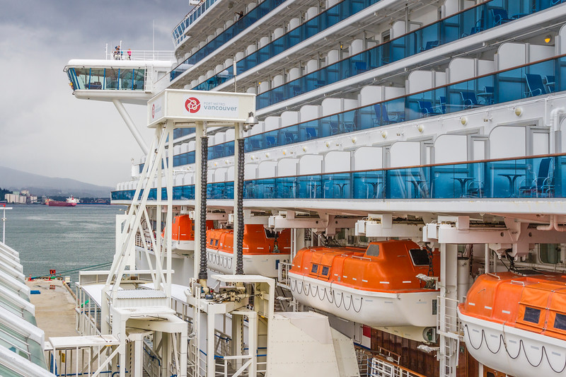 Dock workers loading supplies and luggage onto Golden Princess Cruise Ship, and generally preparing ship for departure, at Canada Place Cruise Ship Terminal at Vancouver Harbor in downtown Vancouver, British Columbia, Canada.