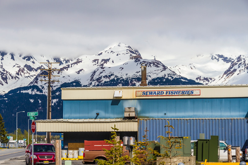 Seward, Alaska, harbor and shipping operations area with beautiful backdrop of snow covered mountains.