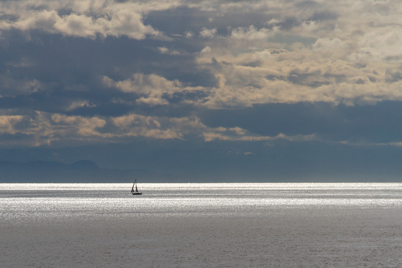 Silhouette of sailboat in light shafts from sun coming through rain clouds, in Vancouver harbor, Vancouver, British Columbia, Canada.