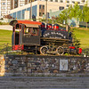 Alaska Railroad historical train statue with downtown Anchorage hotels in background.