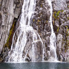 Waterfalls cascading down the Harris Peninsula cliffs in Cataract Cove in Harris Bay in Kenai Fjords National Park. These source of these waterfalls is an alpine glacier 2500 feet above on the ridge of the Peninsula.