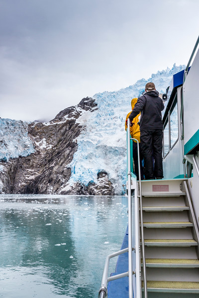 Tourists on Kenai Fjords tour boat enjoying a cold moment looking at Northwestern Glacier in Kenai Fjords National Park.