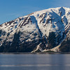 Early morning light on beautiful blue waters of Turnagain Arm, an arm of Cook Inlet (which almost surrounds Anchorage, Alaska). Reflections of snow streak the water.
