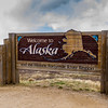 """""""Welcome to Alaska"""" sign at Poker Creek, Alaska, site of the US and Canada border and customs office on the """"Top of the World Highway"""" (also known as Yukon 9). This highway between Dawson City, Yukon Territory, and  Tetlin Junction, Alaska, is named for the way it follows the crest of the hills, providing incredible views of the valleys below. A traveler here definitely has the feeling of being """"on top of the world."""" This basically unpaved highway (because of the stress of the severity of winter cold) is only open in the summer."""
