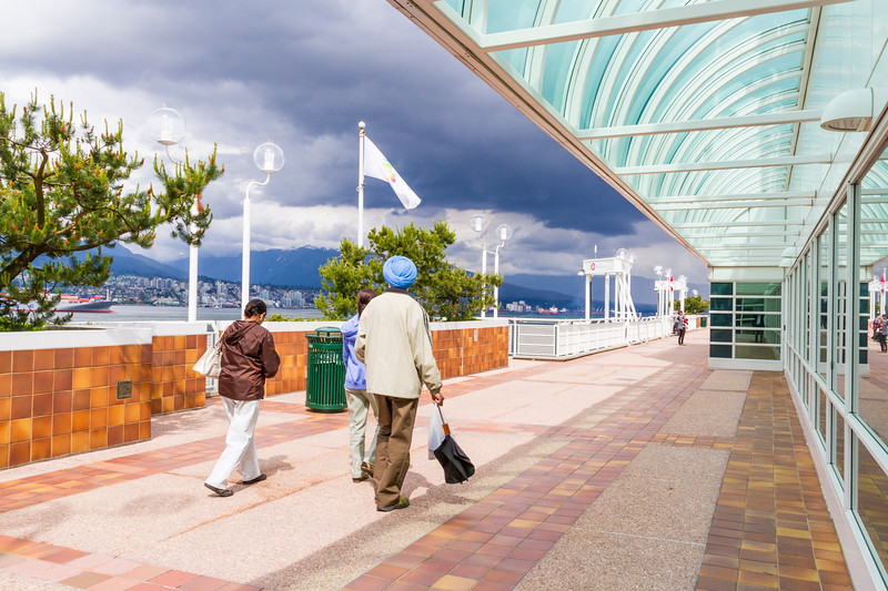 Tourists enjoying Canada Place entertainment center and Cruise Ship Terminal at Vancouver Harbor in downtown Vancouver, British Columbia, Canada.