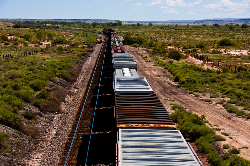 Burlington Northern and Santa Fe Train traveling east parallel to Interstate 40 across the Petrified Forest National Park in Arizona.
