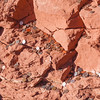 """Coins tossed on red rock hillside at Chapel of the Holy Cross in Sedona, Arizona, in spite of signs requesting that ask visitors to refrain from this superstitious """"make a wish"""" practice."""