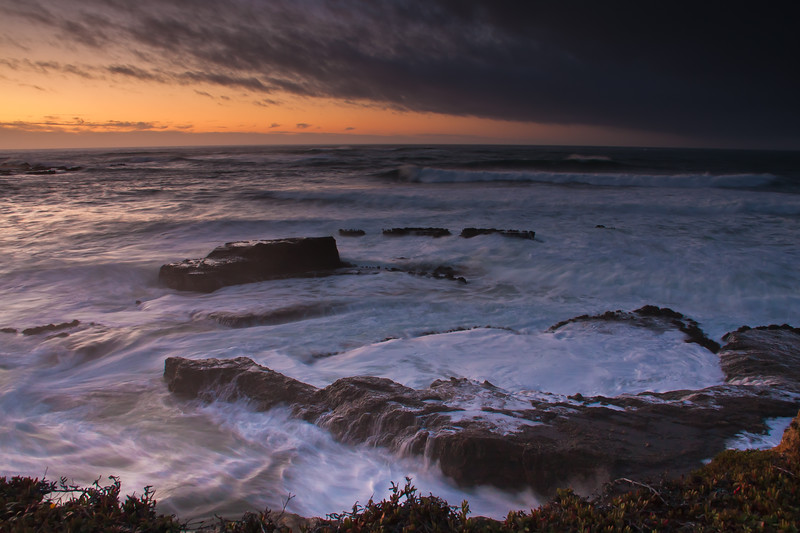 Sunset with stormy weather and high surf at Point Arena Lighthouse peninsula on the rocky pacific coast of northern California. The white-capped, crashing waves swirling over the rocks seem almost ghostly in the twilight, The Point Arena Lighthouse on this peninsula was built in 1870, and later rebuilt with reinforced concrete after the 1906 earthquake.