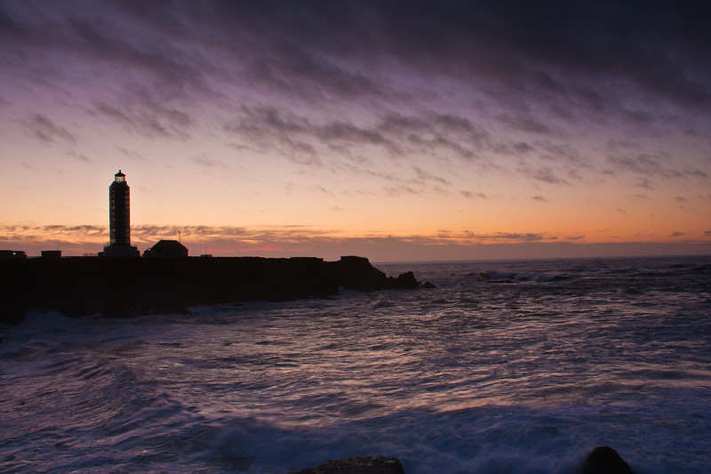 Point Arena Lighthouse at sunset, with storm coming in off the pacific ocean with high surf and crashing waves. The lighthouse is located on the Point Arena peninsula on the northern coast of California. It was oriignally completed in 1870, but was rebuilt with reinforced concretet after the original was destroyed by an earthquake in 1906.