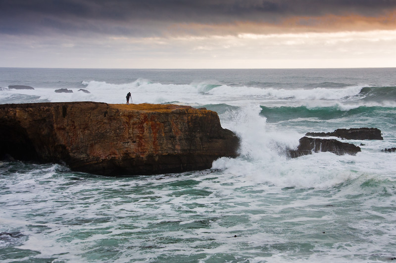 Photographer on cliff at Point Arena on the rocky pacific coast of northern California. Storm coming in from the west is creating high surf and white-capped crashing waves, breaking over rocks and cliffs, just prior to sunset.