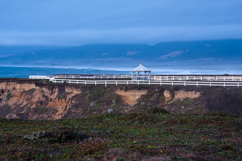 Gazebo and fence at twilight with storm and high surf on Point Arena Lighthouse peninsula on the rocky pacific coast of northern California.