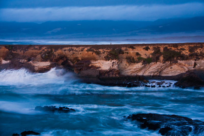 Twilight blue storm clouds and crashing waves just after sunset contrast with the cliffs at Point Arena Lighthouse peninsula on the rocky pacific coast of northern California.