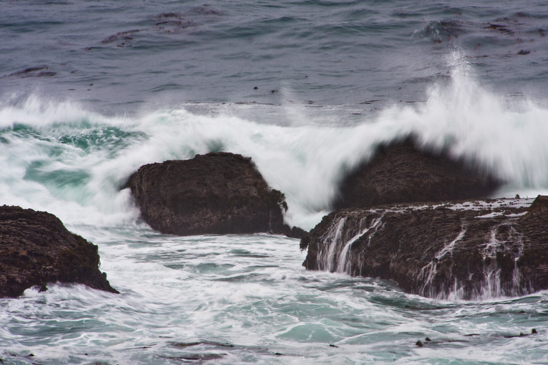 White-capped crashing waves and high surf off the rocky coastline of Point Arena Lighthouse on the pacific coast of northern california. Dramatic displays of ocean waves breaking over rocky ledges occur frequently on the northern pacific coast.