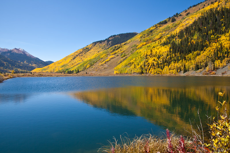Reflections in lake and autumn color at Red Mountain Creek on the Million Dollar Highway (US 550) portion of the San Juan Skyway Scenic Byway in Colorado. The San Juan Skyway is an incredibly beautiful loop of designated Colorado State Highways covering 236 miles in Southwest Colorado.