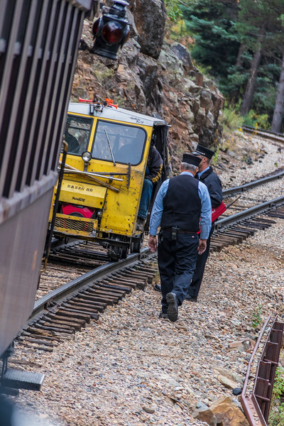 Train conductor checking with hotshot inspector on Durango and Silverton Narrow Gauge Railroad trip through San Juan National Forest in Colorado.