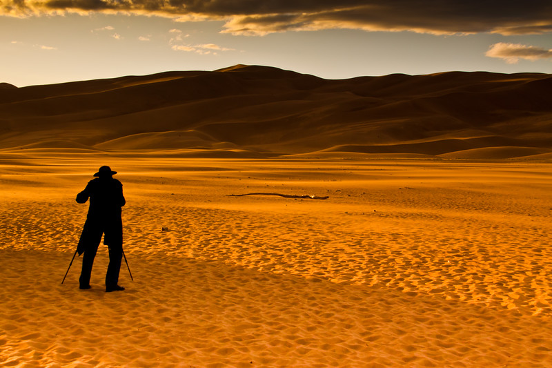 Silhouette of Photographer, Nolan Braud (who is legally blind), at Great Sand Dunes National Park in Colorado at Sunset with strong wind blowing as storm clouds gather. These sand dunes are the tallest dunes in North America.