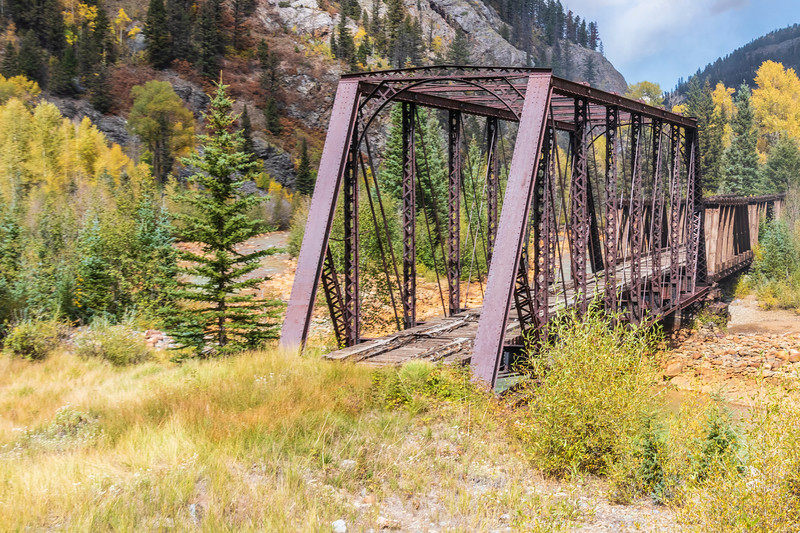 Old abandoned railroad bridge over the Animas River viewed from Durango and Silverton Narrow Gauge Railroad tourist train trip just before getting to Silverton Colorado.