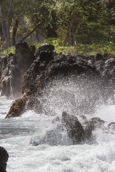 Crashing waves on lava rocks at beach area on Keanae Peninsula, along the Road to Hana on the island of Maui in Hawaii.