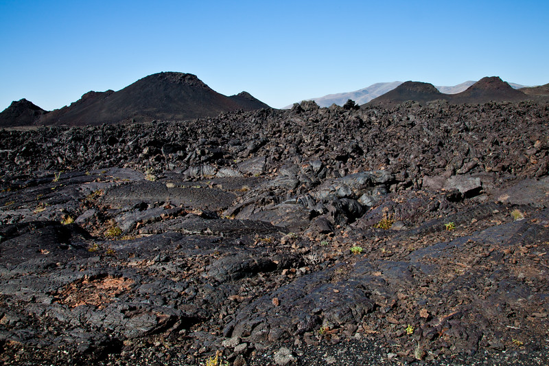 "Rugged Terrain in Craters of the Moon National Monument and Preserve in Idaho. The National Park Service describes the park as ""a vast ocean of lava flows with scattered islands of cinder cones and sagebrush."" Early NASA astronauts trained here because of the terrain. Craters of the Moon sits on top of a rift zone, known as the Great Rift. Since rift zones represent weak areas in the earth's crust, it is common for them to be the site of volcanic eruptions."
