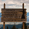 Sign at pass through mountains from Idaho to Wyoming, with view of Jackson Hole from 8400 feet.