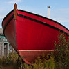 Large red fishing boat in drydock in Lubec, Maine.