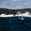 Crashing waves and high winds create a rough ride for small boats coming in to Booth Bay Harbor on the Atlantic Coast of Maine.