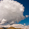 """""""Big Sky"""" cloud formations over barren-looking mountains in southwestern Montana, as rain storm develops in the distance. The treeless expanse contributes to the barren look, although closer inspection reveals that the mountains and foothills are actually covered with a sparse native grass."""