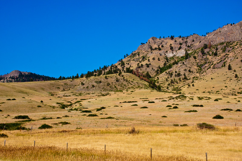 Grasslands and rugged buttes along scenic drive in Montana between Butte and Glacier Nationa Park.