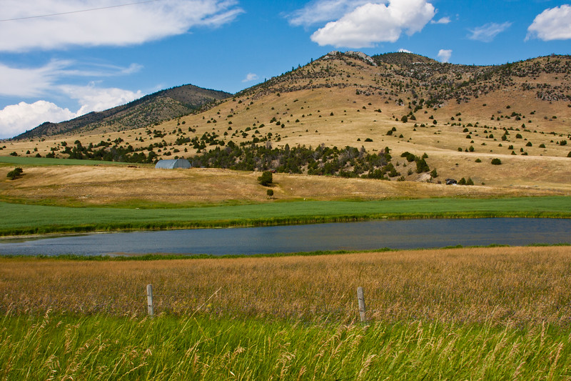 Farm lands and lake along Montana road 359 south of Butte, Montana, with the hills of the Beaverhead-Deerlodge National Forest as background.