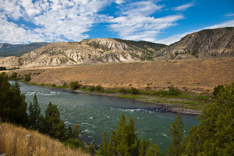 Yellowstone River along scenic highway US 89 in Montana. The Yellowstone river rises in northwestern Wyoming in the Absaroka Range at the Continental Divide. The river starts where the North Fork and the South Fork Yellowstone River converge. It then flows northward through Yellowstone Lake and park and into Montana on its way to North Dakota .  The Yellowstone is the last free flowing river in the lower 48 states of the US. From its headwaters in Lake Yellowstone downstream 670 miles to the Missouri River in North Dakota, the Yellowstone River flows in its natural state, undamed and untamed.