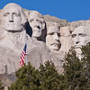 Mount Rushmore National Memorial in South Dakota, a famous patriotic symbol since it was complete in 1941. The Memorial, located 23 miles southwest of Rapid City, is awesome and impressive. The granite faces of four American Presidents tower 5,500 feet above sea level and are scaled to men who would stand 465 feet tall. Each head is as tall as a six-story building! Sculptor Gutzon Borglum's attention to detail makes the faces of George Washington, Thomas Jefferson, Teddy Roosevelt and Abraham Lincoln appear almost lifelike.