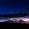 Lightning and thunderstom on horizon with stars in night sky above in Big Bend National Park.