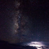 Milky Way and stars above thunderstorm and lightning at the horizon in Big Bend National Park.