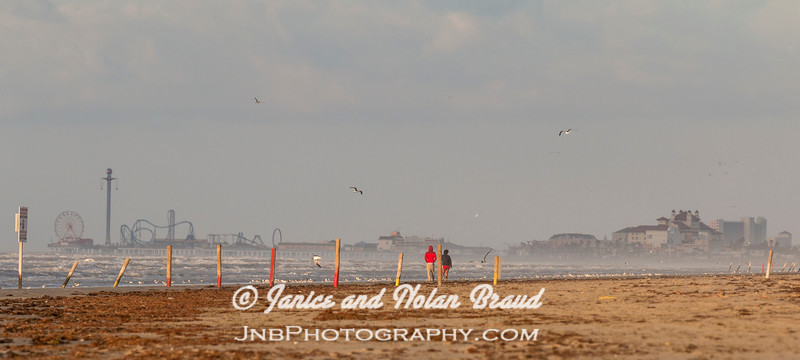 Beach visitors walking in the wind on Galveston East Beach.