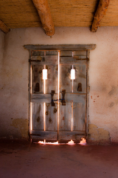 Door backlit by light, in adobe building used as part of movie set, along the Rio Grande River in Texas.