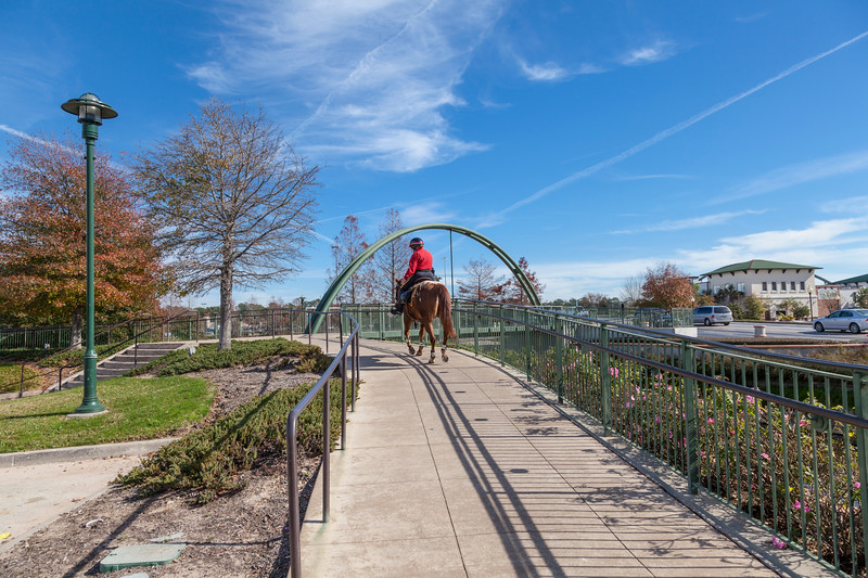 Security patrol horse and rider on the pedestrian walkway and the Woodlands Waterway at the Woodlands Mall.