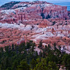First light of sunrise shining on hoodoos at Sunrise Point in Bryce Canyon National Park in Utah. The hoodoos and rock formations are saturated with orange and gold, glowing in the morning light. This viewpoint is the most photographed sunrise viewpoint in the park.