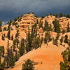 Light before storm at Red Rock Canyon on scenic highway 12 in Dixie National Forest in Utah. This canyon is just a few miles from the entrance to Bryce Canyon National Park, and so is often ignored or bypassed on the way to the better known tourist attraction. However, this canyon displays some of the reddest rock anywhere in Utah, with amazing formations though on a smaller scale. As part of a national forest, it is an interesting and photogenic place to hike and enjoy Utah's wonders.