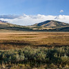 Grasslands in valley with view of Gallatin Mountains in Yellowstone National Park in Wyoming. Deriving its name from Meriwether Lewis and William Clark in honor of Albert Gallatin, Secretary of the Treasury under President Thomas Jefferson, the Gallatins are almost 50 miles long. They begin in Yellowstone Park at Mount Holmes and continue northward to its official end near Bozeman, Montana. At 10,992 feet, Electric Peak is the highest elevation.