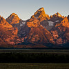 "Sunrise at the Grand Tetons National Park in Wyoming. First light of sun turns the east-facing side of the Grand Tetons Mountain Range a dramatic golden hue. It is rare for the mountain peaks to be completely visible without clouds or fog, as the mountains usually ""make their own weather."""