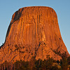 Sunrise on Devil's Tower National Monument in Wyoming. Devils Tower, which rises 1267 feet above the Belle Fourche River, was the first national monument.  It was proclaimed a national monument by President Theodore Roosevelt in 1906.  This 1347 acre park is covered with pine forests, woodlands, and grasslands. Deer, prairie dogs, and other wildlife are seen. Also known as Bears Lodge, it is a sacred site for many American Indians.