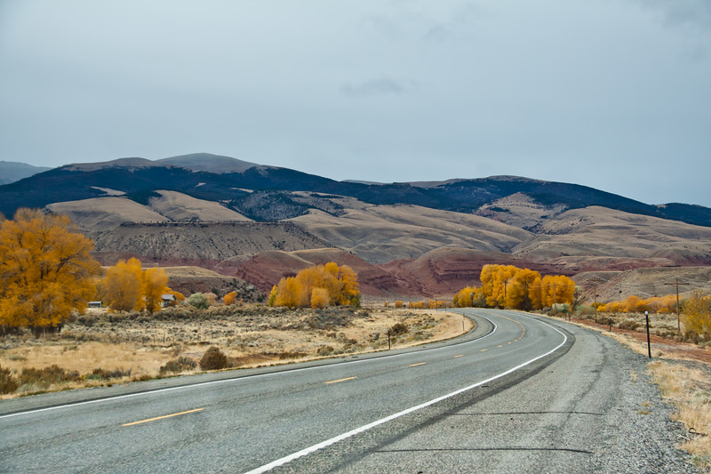 Scenic Highway US 287 in Wyoming in late October. Colorful rocks and mounains and remnants of autumn color make the drive beautiful even with storm clouds in the sky.