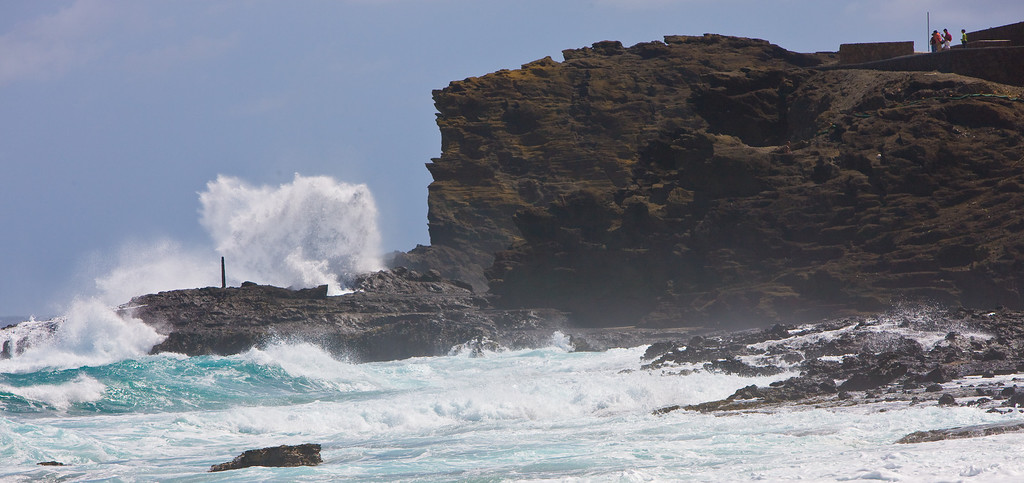 Halona Blowhole seen from Sandy beach. The surf enters a cone shaped natural cave below the waterline. A hole at the end - like a nozzle - releases a powerful water jet.