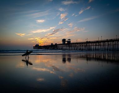 Surfer at dusk at the Oceanside Pier