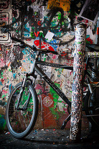 Bicycle resting on a wall of grafitti