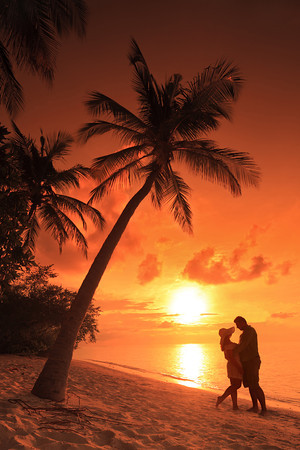 Couple kissing at beach with sunset in the background, Maldives island