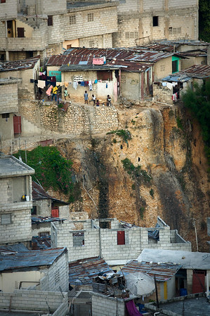 Kids stand outside a house that is perched on the edge of a cliff. Haiti, 2009.