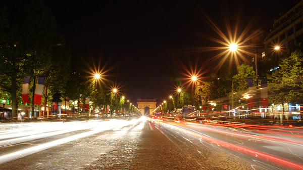 Champs-Elysees avenue at night with the Triumphal Arch in the background