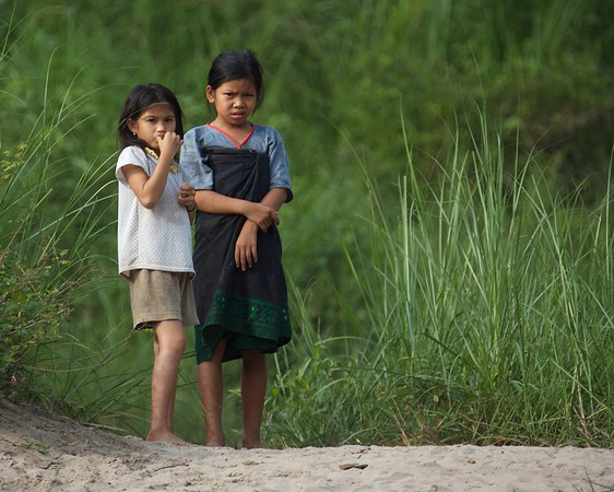 Two Laos girls came down to the riverbank to watch the riverboat.